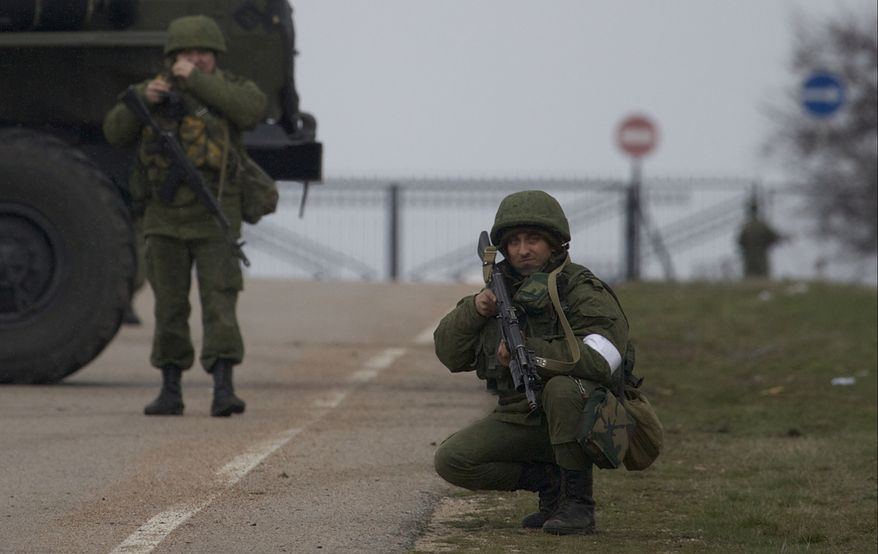 An unidentified gunman holds his assault rifle ready while he and others block the road toward the military airport at the Black Sea port of Sevastopol in Crimea, Ukraine, Friday, Feb. 28, 2014. Russian troops took control of the two main airports in the strategic peninsula of Crimea, Ukraine's interior minister charged Friday, as the country asked the U.N. Security Council to intervene in the escalating conflict. Russian state media said Russian forces in Crimea denied involvement. No violence was reported at the civilian airport in Crimea's capital of Simferopol or at the military airport in the Black Sea port of Sevastopol, also part of Crimea. At the Simferopol airport, a man claiming to speak for the camouflage-clad forces patrolling the airport described them as Crimean militiamen. (AP Photo/Ivan Sekretarev)