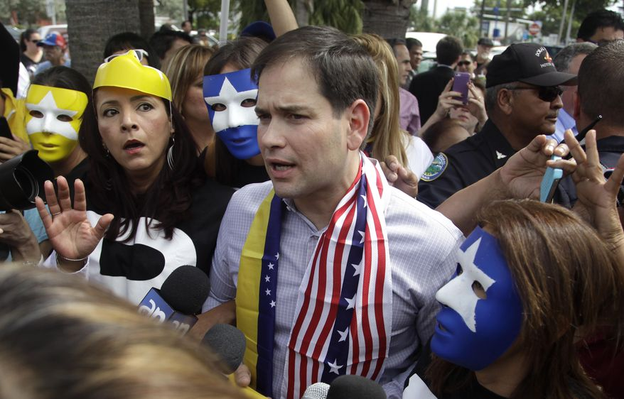 Surrounded by supporters of the Venezuela opposition who wear masks, U.S. Senator Marco Rubio, center, speaks to the media in front of the El Arepazo 2 restaurant on Friday, Feb. 28, 2014 in Doral, Fla. Rubio and Gov. Rick Scott are calling for sanctions against Venezuela, where opponents of President Nicolas Maduro are staging countrywide protests. Both politicians spoke at a press conference in Doral on Friday that drew hundreds of Venezuelans. (AP Photo/Javier Galeano)