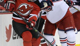 New Jersey Devils' Jaromir Jagr, left, of the Czech Republic, controls the puck as he is checked by Columbus Blue Jackets' Dalton Prout during the second period of an NHL hockey game on Thursday, Feb. 27, 2014, in Newark, N.J. (AP Photo/Bill Kostroun)