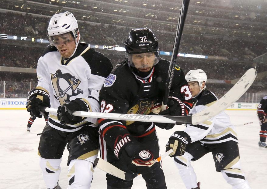 Pittsburgh Penguins left wing James Neal (18) and Chicago Blackhawks defenseman Michal Rozsival (32) look for the puck in the corner during the first period of an NHL Stadium Series hockey game at Soldier Field on Saturday, March 1, 2014, in Chicago. (AP Photo/Charles Rex Arbogast)