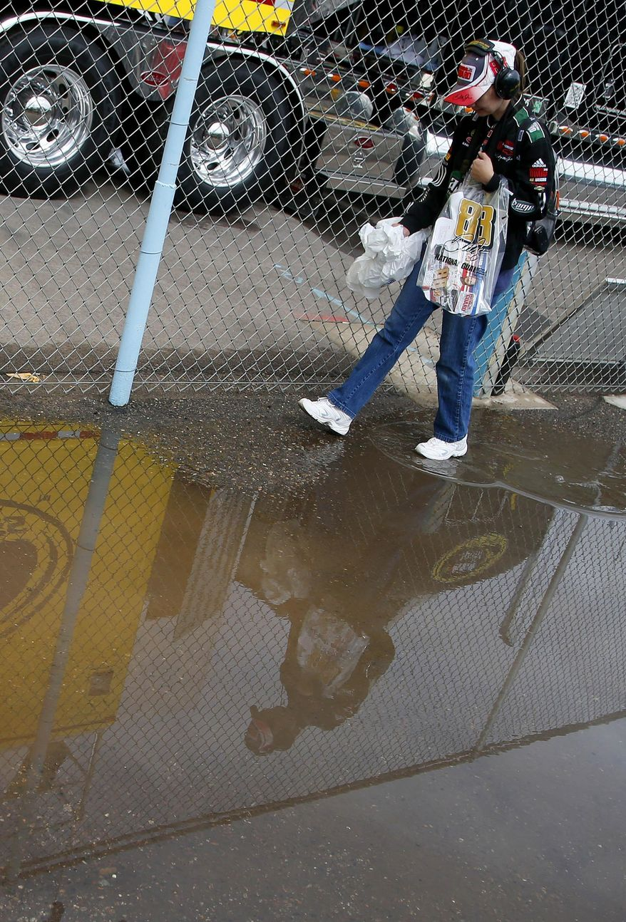 A spectator walks around a puddle caused by overnight rains, prior to a NASCAR Nationwide auto race Saturday, March 1, 2014, in Avondale, Ariz. (AP Photo/Ross D. Franklin)