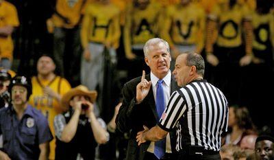 Saint Louis head basketball coach Jim Crews argues a call with an official in the first half of an NCAA college basketball game, Saturday, March 1, 2014 in Richmond, Va. (AP Photo/Jason Hirschfeld)