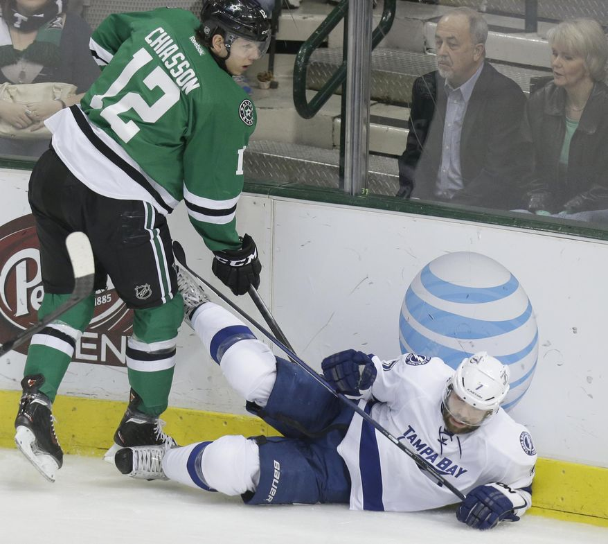Tampa Bay Lightning defenseman Radko Gudas (7) is knocked to the ice by Dallas Stars right wing Alex Chiasson (12) during the second period of an NHL hockey game Saturday, March 1, 2014, in Dallas. (AP Photo/LM Otero)