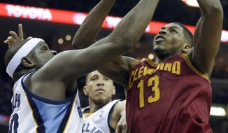 Cleveland Cavaliers' Tristan Thompson (13) gets an offensive rebound over Memphis Grizzlies' Zach Randolph, left, and Tayshaun Prince, center, during the first half of an NBA basketball game in Memphis, Tenn., Saturday, March 1, 2014. (AP Photo/Danny Johnston)