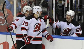 New Jersey Devils' Jaromir Jagr (68) is congratulated by Michael Ryder (17) and Ryane Clowe (29) after Jagr scored his 700th goal in the second period of an NHL hockey game against the New York Islanders on Saturday, March 1, 2014, in Uniondale, N.Y. (AP Photo/Kathy Kmonicek)