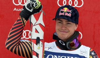 Canada's Erik Guay celebrates on the podium after winning an alpine ski men's World Cup downhill, in Kvitfjell, Norway, Saturday, March 1, 2014. (AP Photo/Alessandro Trovati)