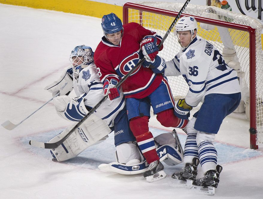 Montreal Canadiens' Daniel Briere is sandwiched between Toronto Maple Leafs goaltender Jonathan Bernier, left, and Toronto's Carl Gunnarsson during the second period of an NHL hockey game in Montreal, Saturday, March 1, 2014. (AP Photo/The Canadian Press, Graham Hughes)