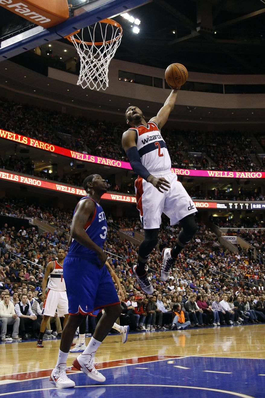 Washington Wizards' John Wall, right, dunks the ball as Philadelphia 76ers' Henry Sims looks on during the first half of an NBA basketball game, Saturday, March 1, 2014, in Philadelphia. (AP Photo/Matt Slocum)