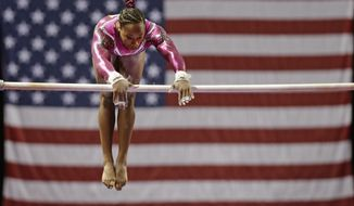 Elizabeth Price performs on the uneven bars during the American Cup gymnastics competition in Greensboro, N.C., Saturday, March 1, 2014. Price won the women's overall title. (AP Photo/Chuck Burton)