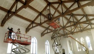 ADVANCE FOR WEEKEND EDITIONS MARCH 1-2 - In this Feb. 12, 2014 photo,  a crew from Barton's Painting, in Seward, sprays finish on trusses in the sanctuary of the United Methodist Church in Friend, Neb. A piece of Friend's religious history nearly vanished the morning of Dec. 4, 2012. A candle left burning overnight started a fire in the sanctuary, and by the time firefighters arrived, smoke was pouring out of the church's three east windows that already had been cracked by the intense heat. (AP Photo/The Journal-Star, Eric Gregory) LOCAL TV OUT; KOLN-TV OUT; KGIN-TV OUT; KLKN-TV OUT