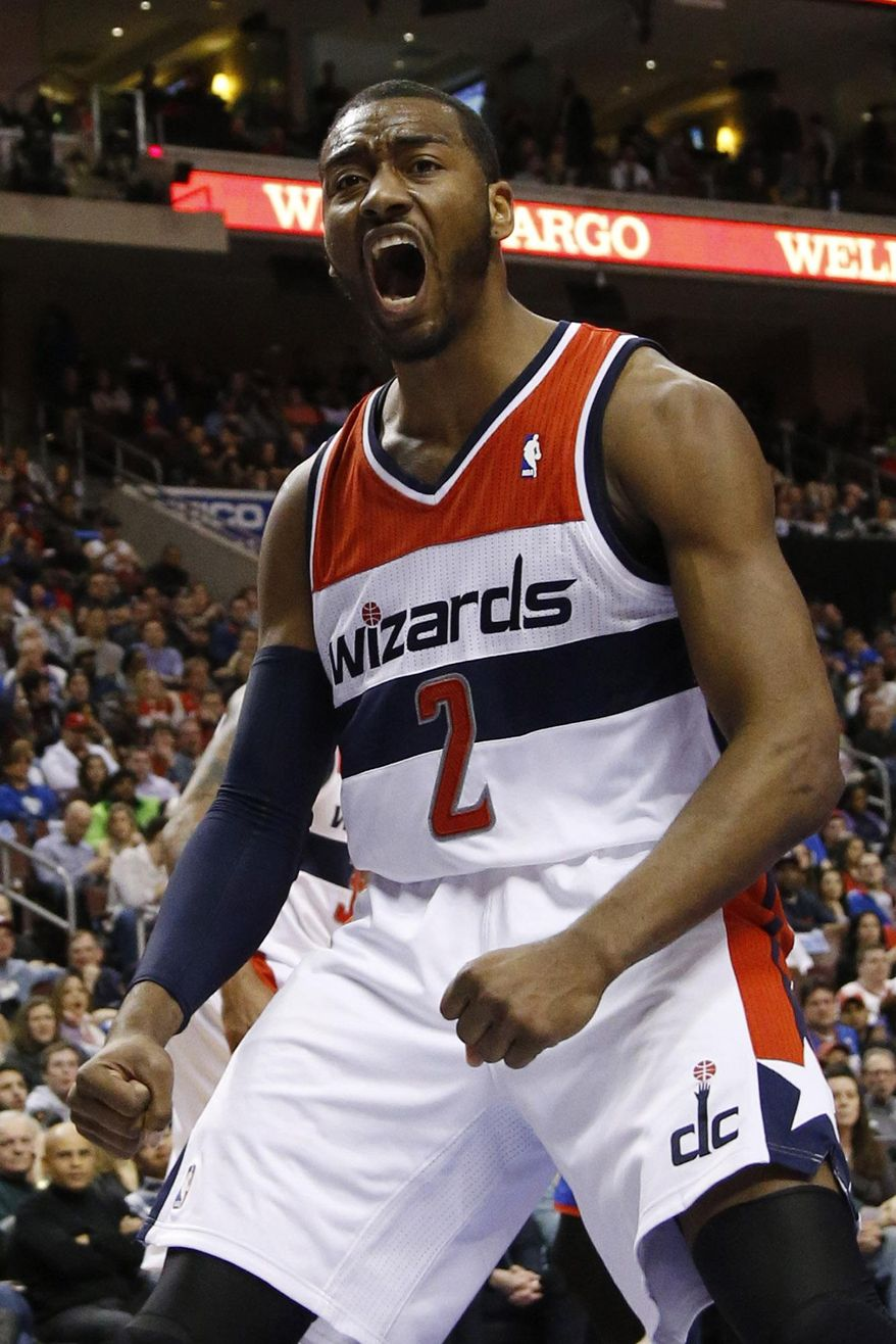 Washington Wizards' John Wall reacts after his dunk during the first half of an NBA basketball game against the Philadelphia 76ers, Saturday, March 1, 2014, in Philadelphia. (AP Photo/Matt Slocum)