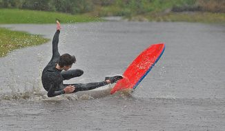 Ryan Springer, 16, surfs a large puddle off in Carpinteria, Calif., Saturday, March 1, 2014. The storm marked a sharp departure from many months of drought that has grown to crisis proportions for the state's vast farming industry. However, such storms would have to become common to make serious inroads against the drought, weather forecasters have said. (AP Photo/Santa Barbara News-Press, Mike Eliason)