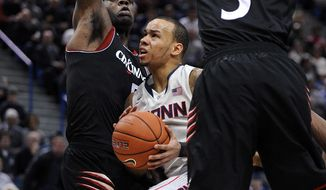 Connecticut's Shabazz Napier, center, drives past Cincinnati's Justin Jackson, left, and Shaquille Thomas (3) during the second half of an NCAA college basketball game in Hartford, Conn., Sunday, March 1, 2014. Napier scored a game-high 18 points and had 11 rebounds in his team's 51-45 victory. (AP Photo/Fred Beckham)