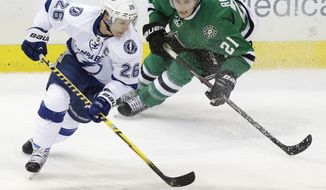 Tampa Bay Lightning right wing Martin St. Louis (26) skates with the puck as Dallas Stars left wing Antoine Roussel (21) closes in during the first period of an NHL hockey game Saturday, March 1, 2014, in Dallas. (AP Photo/LM Otero)