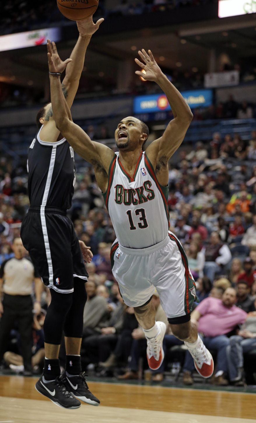 Milwaukee Bucks' Ramon Sessions (13) looses the ball against Brooklyn Nets' Deron Williams in the second half of an NBA basketball game Saturday, March 1, 2014, in Milwaukee. (AP Photo/Jeffrey Phelps)