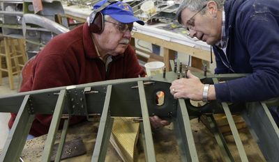 Volunteers Dick Bidlack, left, a 79-year-old Vietnam War fighter pilot, and Steve Taylor work on a horizontal stabilizer for the tail of a B-17 World War II-era bomber being built from salvaged and fabricated parts at the Champaign Aviation Museum in Urbana, Ohio on Thursday, Feb. 20, 2014. (AP Photo/Al Behrman)