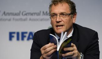 "FIFA Secretary General Jerome Valcke holds the book ""Laws of the Game"" as he speaks during a press conference following the 128 Annual General Meeting of the International Football Association Board IFAB, on Saturday, March 1, 2014, in Zurich, Switzerland. (AP Photo/Keystone,Steffen Schmidt)"