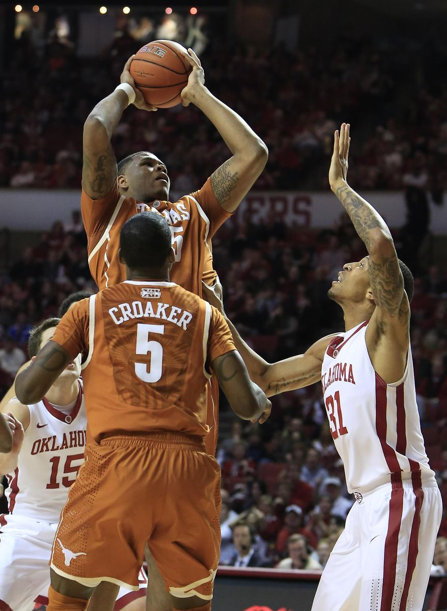 Texas center Cameron Ridley (55) shoots over Oklahoma forward Cameron Clark (21) as Texas guard Damaercus Croaker (5) watches during the first half of an NCAA college basketball game in Norman, Okla., Saturday, March 1, 2014. (AP Photo/Alonzo Adams)