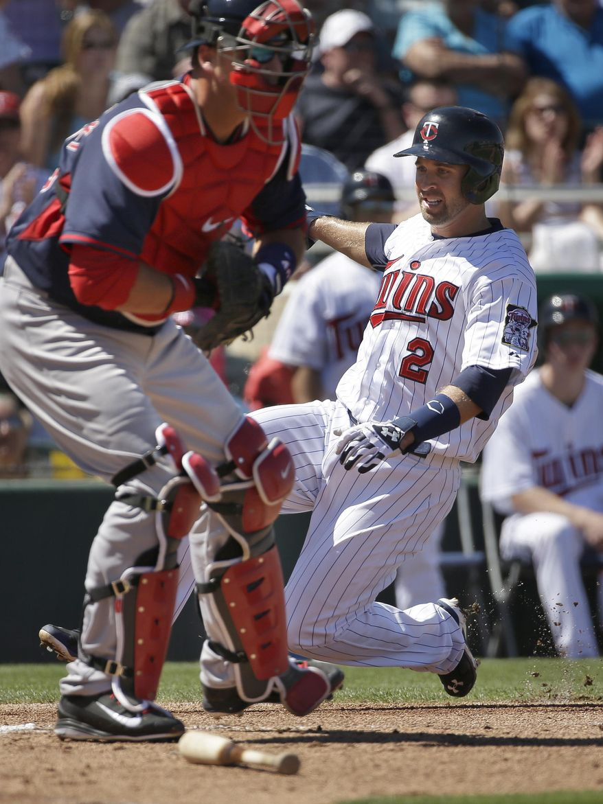 Minnesota Twins' Brian Dozierin, right, scores on an RBI single by Joe Mauer as Boston Red Sox catcher A.J. Pierzynski, left, tries to make the play in the first inning of an exhibition baseball game, Saturday, March 1, 2014, in Fort Myers, Fla. (AP Photo/Steven Senne)