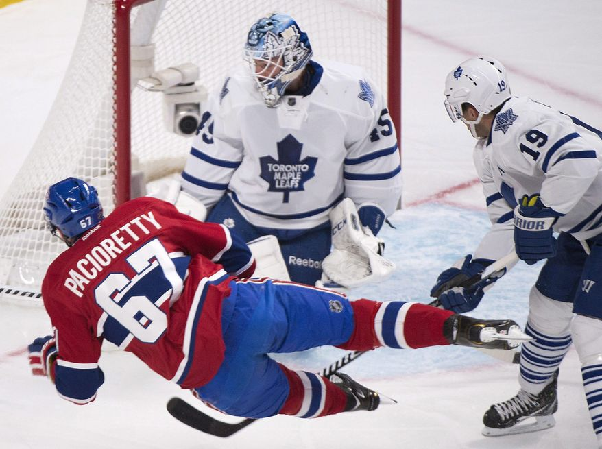 Montreal Canadiens' Max Pacioretty (67) takes a shot against Toronto Maple Leafs goaltender Jonathan Bernier as Leafs' Joffrey Lupul, right, defends during the first period of an NHL hockey game in Montreal, Saturday, March 1, 2014. (AP Photo/The Canadian Press, Graham Hughes)