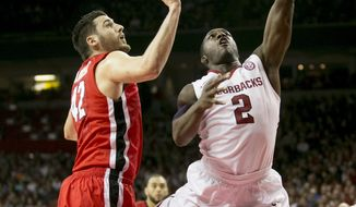 Arkansas forward Alandise Harris (2) goes up for a layup around Georgia forward Nemanja Djurisic (42) during the first half of an NCAA college basketball game on Saturday, March 1, 2014, in Fayetteville, Ark. (AP Photo/Gareth Patterson)