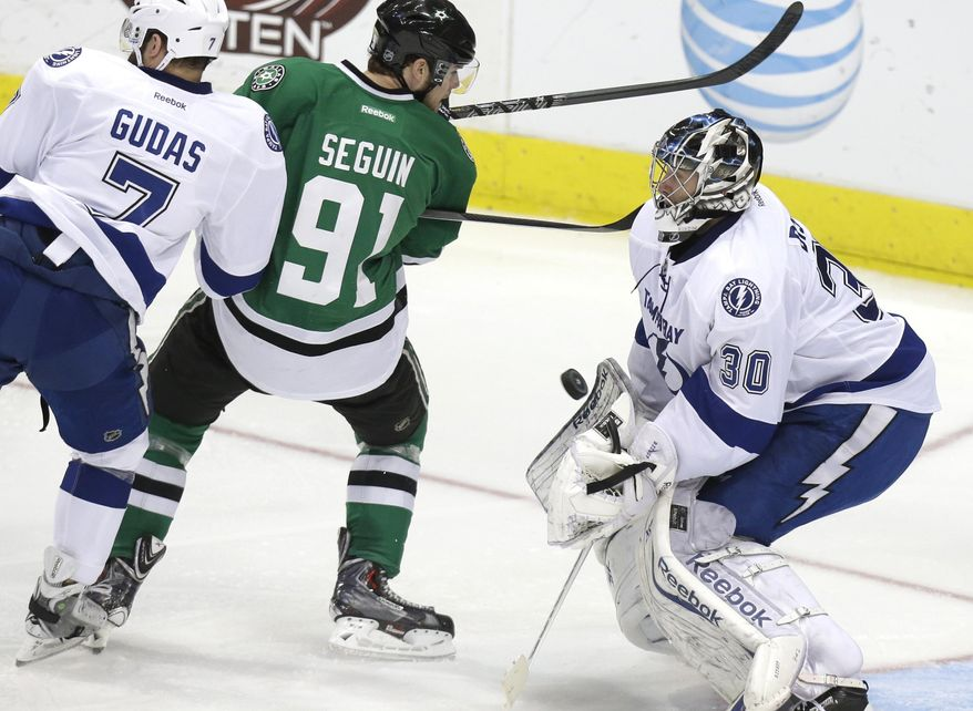 Tampa Bay Lightning goalie Ben Bishop (30) blocks a shot against Dallas Stars center Tyler Seguin (91) as Lightning defenseman Radko Gudas (7) lends a hand during the second period of an NHL hockey game Saturday, March 1, 2014, in Dallas. (AP Photo/LM Otero)