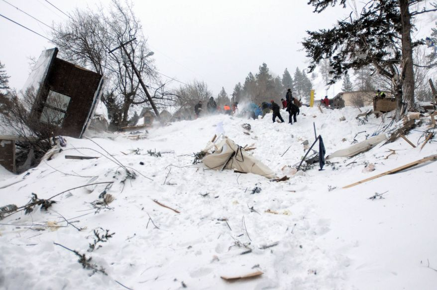 Rescuers dig at the scene of an avalanche in Missoula's Rattlesnake Valley on Friday, Feb. 28, 2014. The avalanche roared into a residential neighborhood and destroyed a house, but three people were found alive amid the snow and wreckage, police said. The survivors were an elderly couple and an 8-year-old boy, police Sgt. Travis Welsh said.  (AP Photo/The Missoulian, Tom Bauer)
