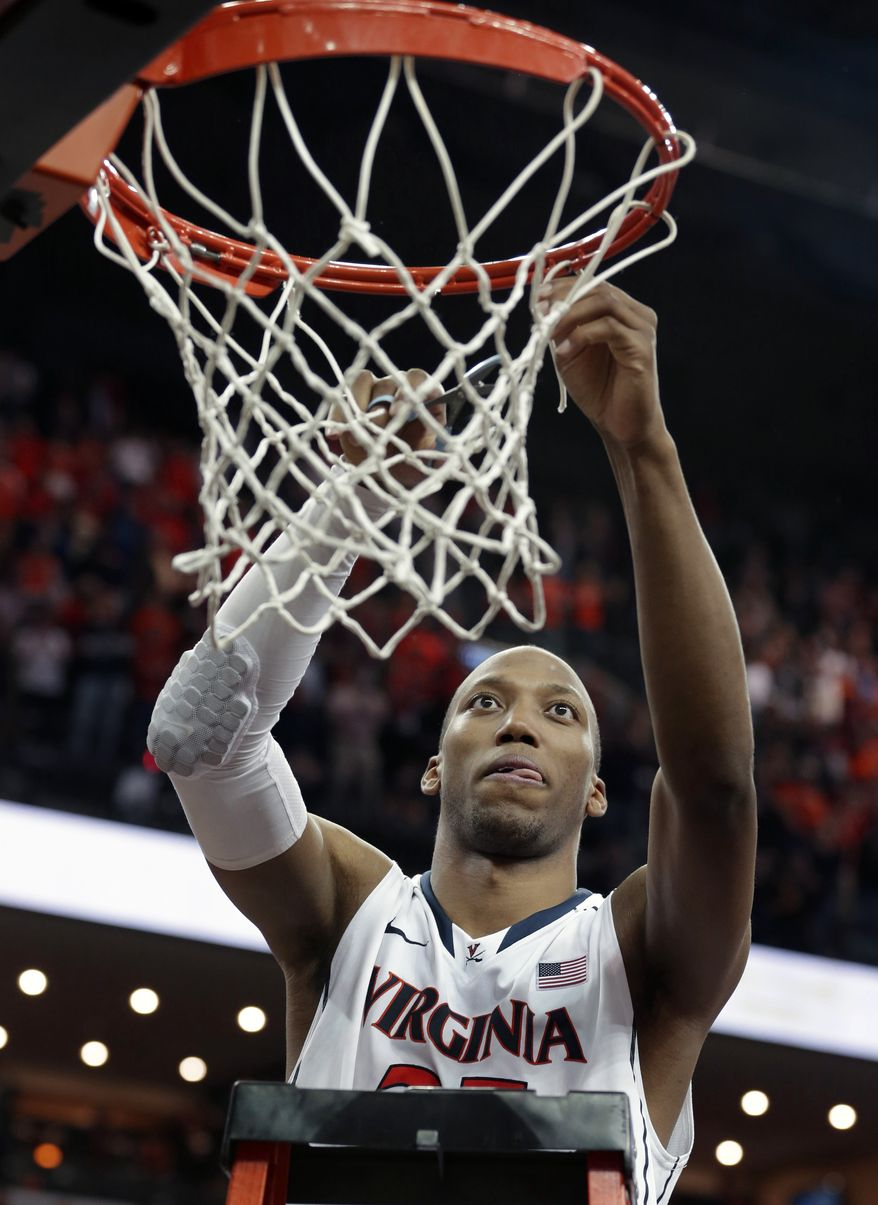 Virginia forward Akil Mitchell (25) cuts down the net after thie win over Syracuse in Charlottesville, Va., Saturday, March 1, 2014. Virginia won the game 75-56. (AP Photo/Steve Helber)