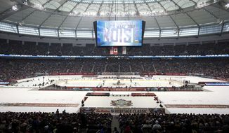 The Vancouver Canucks and Ottawa Senators take the opening face-off of an NHL Heritage Series hockey game in Vancouver, British Columbia, on Sunday, March 2, 2014. (AP Photo/The Canadian Press, Darryl Dyck)