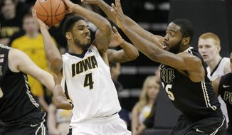 Iowa guard Roy Devyn Marble (4) is double-teamed by Purdue guard Rapheal Davis, right, and guard Ronnie Johnson, behind Marble, during the first half of a Big Ten NCAA college basketball game at Carver-Hawkeye Arena on Sunday, March 2, 2014, in Iowa City, Iowa. (AP Photo/Jim Slosiarek)