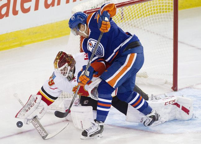 Calgary Flames goalie Reto Berra (29) makes the save on Edmonton Oilers' David Perron (57) during the second period of an NHL hockey game Saturday, March 1, 2014, in Edmonton, Alberta. (AP Photo/The Canadian Press, Jason Franson)