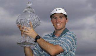 Russell Henley holds up his trophy after winning the Honda Classic golf tournament on Sunday, March 2, 2014, in Palm Beach Gardens, Fla. (AP Photo/Wilfredo Lee)