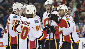 Calgary Flames Sean Monahan (23), Markus Granlund (60), Joe Colborne (8) and Mark Giordano (5) celebrate a goal against the Edmonton Oilers during the first period of an NHL hockey game, Saturday, March 1, 2014 in Edmonton, Alberta. (AP Photo/The Canadian Press, Jason Franson)