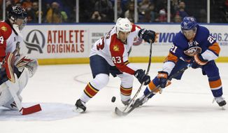 Florida Panthers defenseman Mike Weaver (43) defends in front of the crease with New York Islanders right wing Kyle Okposo (21) defending in the second period of an NHL hockey game at Nassau Coliseum in Uniondale, N.Y., Sunday, March 2, 2014. Florida Panthers goalie Tim Thomas, left, looks on. (AP Photo/Kathy Willens)