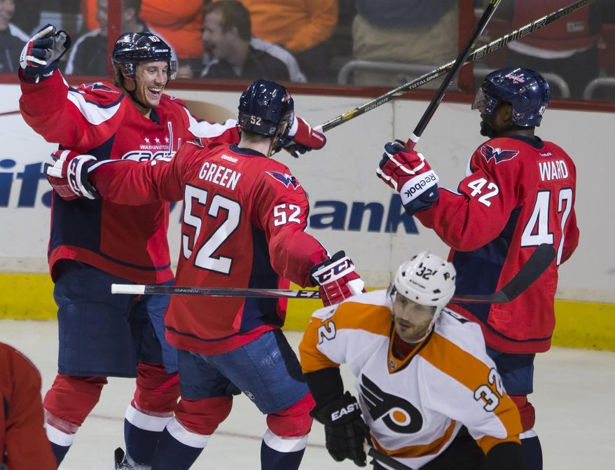 Philadelphia Flyers defenseman Mark Streit (32) skates off as Washington Capitals center Jay Beagle, left, celebrates his goal with teammates Mike Green, second from left, and Joel Ward during the second period of an NHL hockey game on Sunday, March 2, 2014, in Washington. (AP Photo/ Evan Vucci)