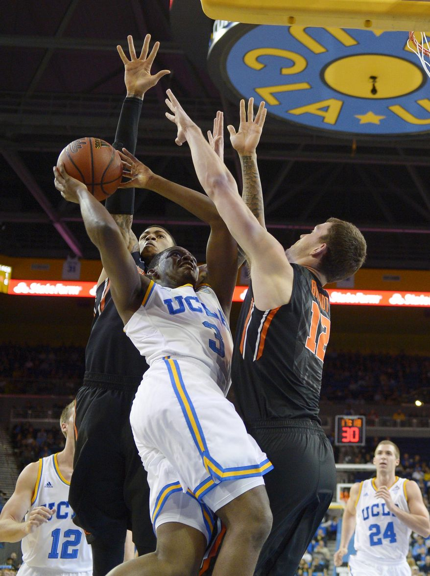 UCLA guard Jordan Adams, center, puts up a shot as Oregon State forward Eric Moreland, left, and center Angus Brandt defend during the first half of an NCAA college basketball game, Sunday, March 2, 2014, in Los Angeles. (AP Photo/Mark J. Terrill)