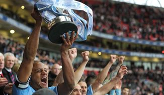 Manchester City captain Vincent Kompany lifts the English League Cup trophy after defeating Sunderland in the final at Wembley Stadium, London Sunday March 2, 2014. City won the match 3-1. (AP Photo/Adam Davy/Pool)