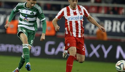 Panathinaikos' Marcus Berg, left,  scores his team's second goal as Olympiakos' Avraam Papadopoulos looks the ball during a Greek League soccer match at Georgios Karaiskakis stadium, in Piraeus port, near Athens, on Sunday, March 2, 2014. (AP Photo/Thanassis Stavrakis)