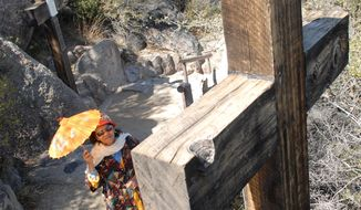 This March 6, 2007 photo, a  visitor walks along the cross path at the Shrine of St Joseph in Yarnell, Ariz.,  while making a day trip with the Golden Hearts group from St Thomas The Apostle Parish in Phoenix.  Barney Wasson's ashes were laid to rest next to his parents and brother at the Shrine of St. Joseph of the Mountains, which they built on their land in Yarnell 74 years ago.  (AP Photo/The Daily Courier, Les Stukenberg)