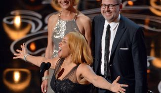 """Darlene Love, center, sings as Janet Friesen, background left, and Morgan Neville accept the award for best documentary feature for """"20 Feet from Stardom"""" during the Oscars at the Dolby Theatre on Sunday, March 2, 2014, in Los Angeles.  (Photo by John Shearer/Invision/AP"""