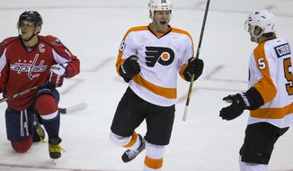 Washington Capitals right wing Alex Ovechkin, left, kneels on the ice as Philadelphia Flyers right wing Adam Hall, center, celebrates his goal with defenseman Braydon Coburn during the first period of an NHL hockey game on Sunday, March 2, 2014, in Washington. (AP Photo/ Evan Vucci)