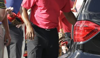 Tiger Woods loads a vehicle as he prepares to leave after withdrawing having played 13 holes in the final round of the Honda Classic golf tournament on Sunday, March 2, 2014, in Palm Beach Gardens, Fla. (AP Photo/Wilfredo Lee)