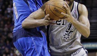 San Antonio Spurs' Tim Duncan (21) is pressured by Dallas Mavericks' Samuel Dalembert (1) during the first half of an NBA basketball game, Sunday, March 2, 2014, in San Antonio. (AP Photo/Eric Gay)