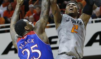 Oklahoma State wing Le'Bryan Nash (2) shoots in front of Kansas forward Tarik Black (25) during the second half of an NCAA college basketball game in Stillwater, Okla., Saturday, March 1, 2014. Oklahoma State won 72-65. (AP Photo/Sue Ogrocki)