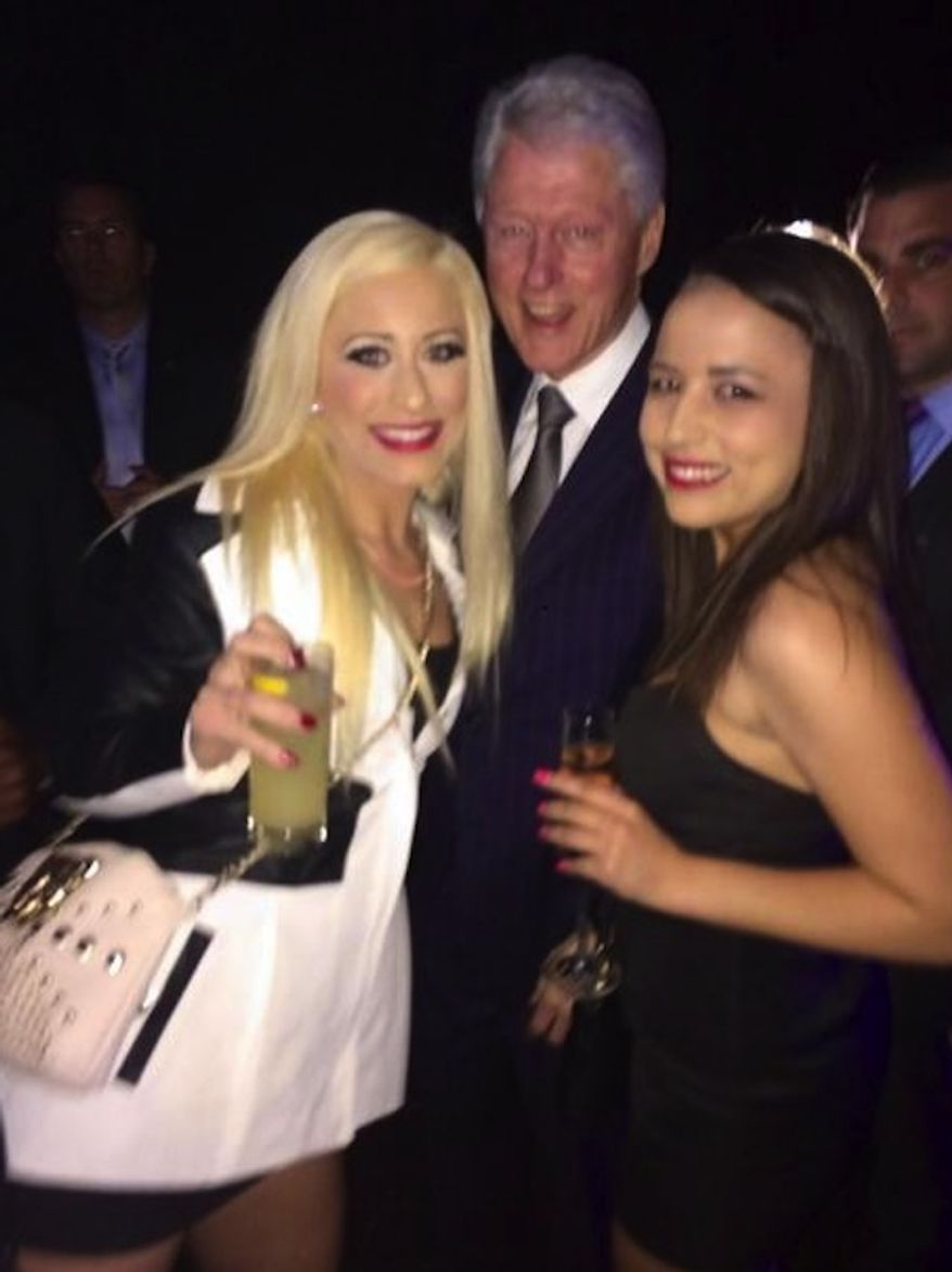Former President Bill Clinton posed for a photo at an event Thursday night with two women who work as legal prostitutes at the Moonlite Bunny Ranch in Nevada. (Facebook: Moonlite Bunny Ranch)