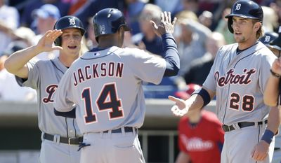 Detroit Tigers' Austin Jackson, center, celebrates with teammates Andy Dirks, left, and Jordan Lennerton, right, after the three players scored on a double by teammate Nick Castellanos during the first inning of an exhibition baseball game against the Detroit Tigers Friday, Feb. 28, 2014, in Clearwater, Fla. (AP Photo/Charlie Neibergall)