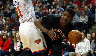 Chicago Bulls shooting guard Jimmy Butler, right, tries to get around New York Knicks shooting guard Iman Shumpert, left, during the second half of an NBA basketball game on Sunday, March 2, 2014, in Chicago. The Bulls won the game 109-90. (AP Photo/Jeff Haynes)