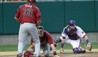 South Carolina's Grayson Greiner, center, celebrates with teammate Kyle Martin after diving around Clemson catcher Chris Okey, right, to score the tying run in an NCAA college baseball game on Sunday, March 2, 2014, in Clemson, S.C. (AP Photo/Anderson Independent-Mail, Mark Crammer) GREENVILLE NEWS OUT; SENECA NEWS OUT
