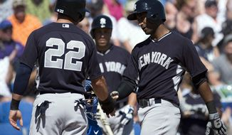 New York Yankees' Eduardo Nunez, right, is congratulated by Jacoby Ellsbury after hitting a two-run home run off Toronto Blue Jays' Todd Redmond during the third inning of an exhibition baseball game in Dunedin, Fla., on Sunday, March 2, 2014. (AP Photo/The Canadian Press, Frank Gunn)