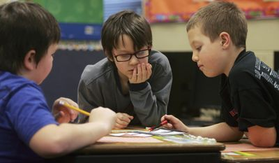 FILE  - In this Jan. 10, 2014 file photo Blake Van Ningen, left, Ashton Cushing, center, and Zac Sayler work on an assignment at Freeman Elementary in Freeman, S.D. Legislative leaders say that stagnating state tax collections could hamper efforts to give school districts extra state aid to help them recover from budget cuts imposed three years ago The House Speaker Brian Gosch says lawmakers have to make sure they can fund existing programs before trying to spend extra on schools and other priorities. (AP Photo/Jeremy Waltner, File)